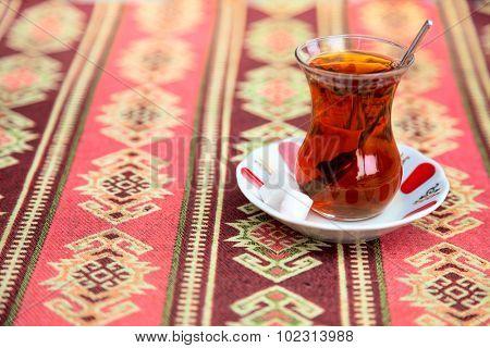 Turkish tea in traditional glass cup on handmade arabic ornamental tablecloth, travel in Turkey