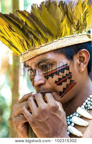 Native Brazilian guy playing wooden flute at an indigenous tribe in the Amazon