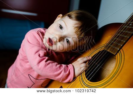 Small toddler listening and singing to sounds coming out of a guitar. Musical education tactile experiences and learning concept. poster