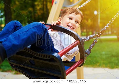 smiley little boy riding on a swing and looking at something in a park