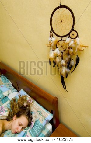 Girl Sleeping In Bed With Dreamcatcher Above