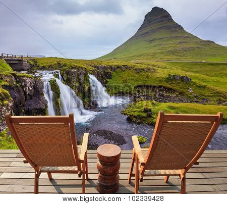 Threaded full-flowing waterfall Kirkyufell Foss on the grassy mountains. Deck chairs on the wooden floor waiting for tourists