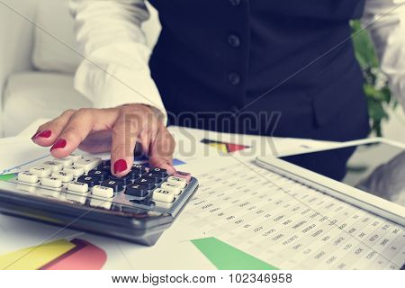 a businesswoman using an electronic calculator in her office, with a desk full of charts and a sheet of accounts