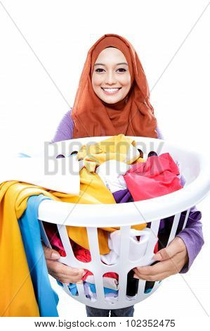 Housewife Wearing Hijab Carrying Laundry Basket Full Of Dirty Clothes