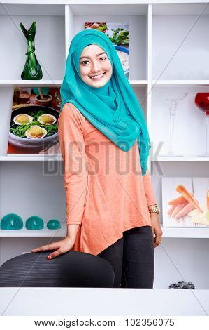 Beautiful Young Woman Wearing Hijab Standing With Shelf And Some Ornaments At Background