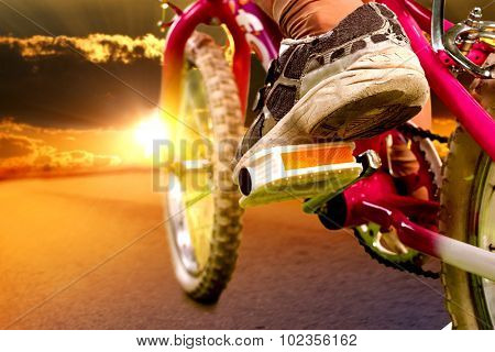Low section of child food riding on bike to mountain.
