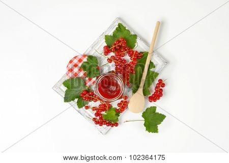 overhead view of opened jar filled with red currant jam and served on the wooden cutting board with wooden spoon