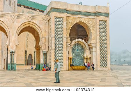 CASABLANCA, MOROCCO, APRIL 2, 2015: People gather on the outside grounds of Hassan II Mosque or Grande Mosquee Hassan II by misty morning