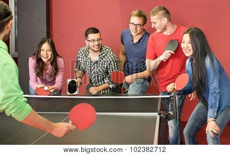 Group of happy young friends playing ping pong table tennis - Fun moment in game room of traveler youth hostel - Concept of vintage sport and genuine emotions - Main focus on two guys with eye glasses poster