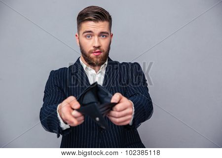 Portrait of a handsome businessman showing his empty wallet over gray background poster