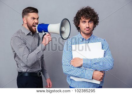 Angry businessman screaming via megaphone to another man over gray background