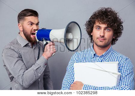Angry businessman yelling via megaphone to another man over gray background