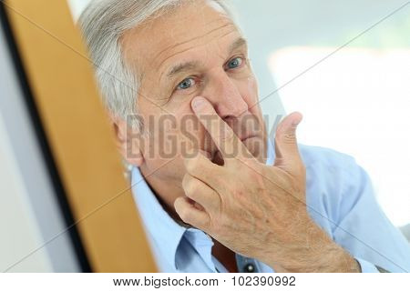 Senior man applying anti-aging lotion on his face poster
