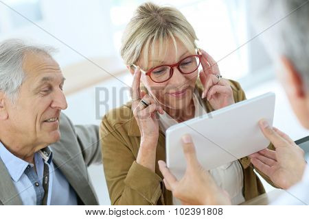 Senior woman trying new eyeglasses on poster