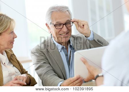 Senior man trying new eyeglasses on, optical store