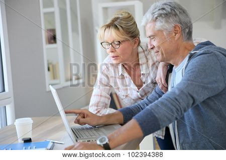 Senior couple at home checking expenses on internet poster