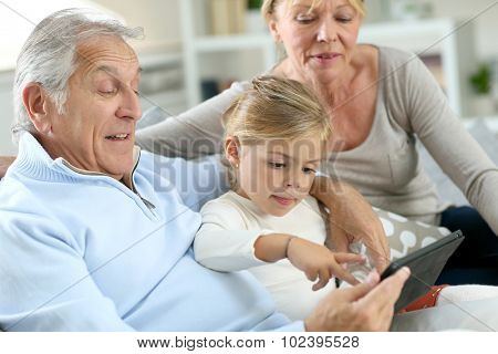 Grandparents with little girl using digital tablet