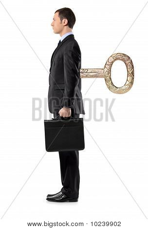 Full Length Portrait Of A Businessman With Wind-up Key In His Back