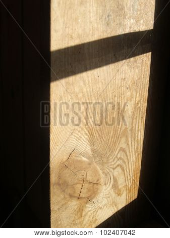 The weathered wooden planks with window shadow