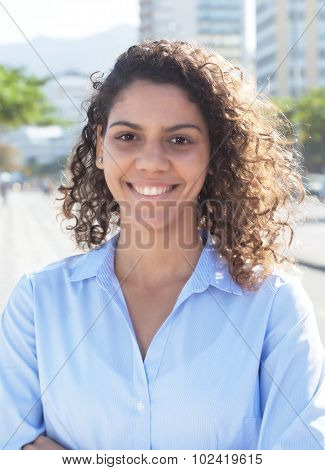 Laughing latin woman with blue blouse in a city of latin america with modern buildings and trees in the background poster