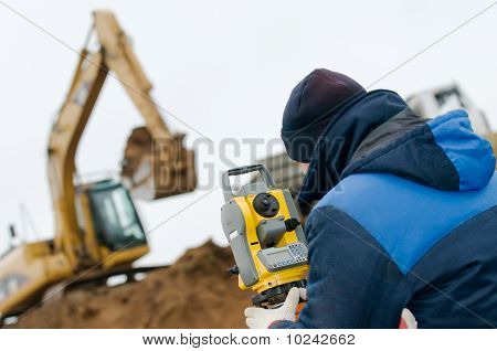 surveyor worker with geodesy equipment device theodolite at land surveying outdoors poster
