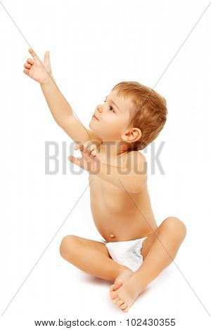 Baby boy in pampers pointing up, isolated on white