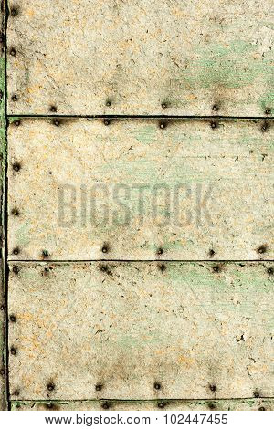 Old green bleached fiberboard wall with nails