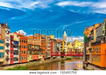 Colorful yellow and orange houses and Eiffel Bridge, Old fish stalls, reflected in water river Onyar, in Girona, Catalonia, Spain. Church of Sant Feliu at background. poster
