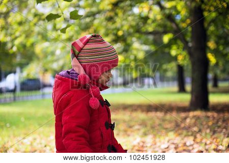 Girl in a red coat walks in autumn park poster