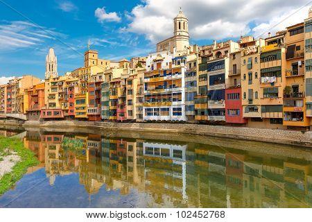 Colorful yellow and orange houses and famous house Casa Maso reflected in water river Onyar, in Girona, Catalonia, Spain. Church of Sant Feliu and Saint Mary Cathedral at background. poster