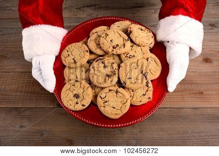 Closeup high angle view of Santa Claus serving cookies. Only santa's hands are shown as he holds a red tray filled with chocolate chip cookies over a rustic wood table.