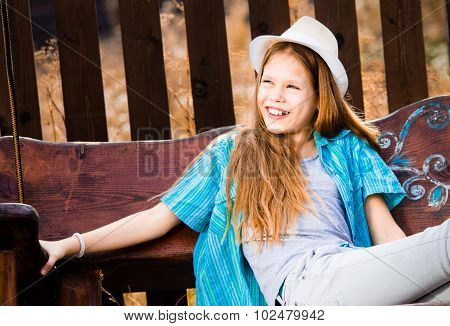 Smiling Girl On Garden Swing