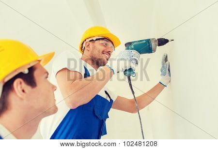 building, teamwork, working equipment and people concept - group of smiling builders s in hardhats with electric drill indoors
