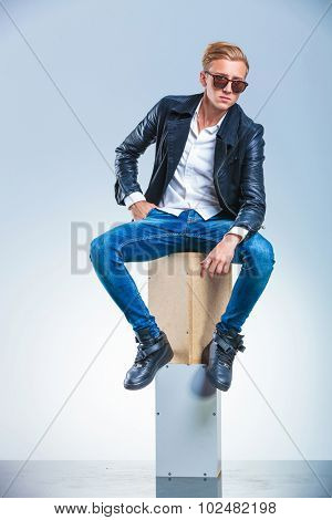 young boy holding his hand in pocket is posing while sitting on boxes with sunglasses on