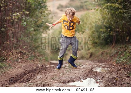 Boy In Gumboots Jumps Into The Puddle