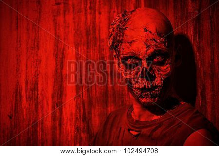 Frightening bloody zombie man in blood-red light. Halloween. poster