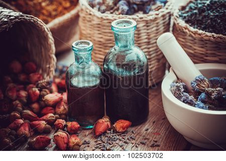 Bottles Of Tincture, Basket With Rose Buds, And Dried Forget Me Not Flowers In Mortar. Herbal Medici