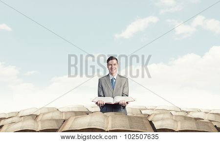 Young smiling businessman with opend book in hands