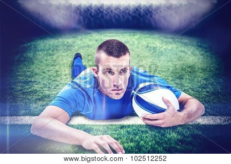 Rugby player looking away while lying in front with ball against rugby pitch