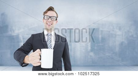 Happy geeky businessman holding coffee mug against city scene in a room