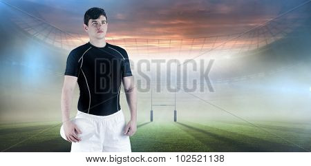 Rugby player holding a rugby ball against rugby pitch