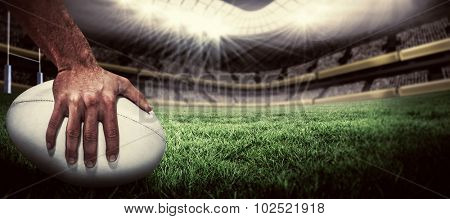 Close-up of sports player holding ball against rugby pitch