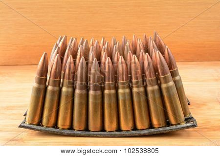 Several stacked clips of 7.62x39 caliber ammunition on wooden background poster