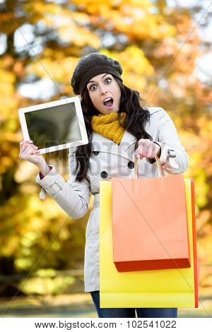 Amazed Woman Holding Shopping Bags And Tablet In Autumn
