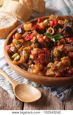 Italian appetizer Caponata with eggplants close-up on a wooden plate. Vertical rustic style poster