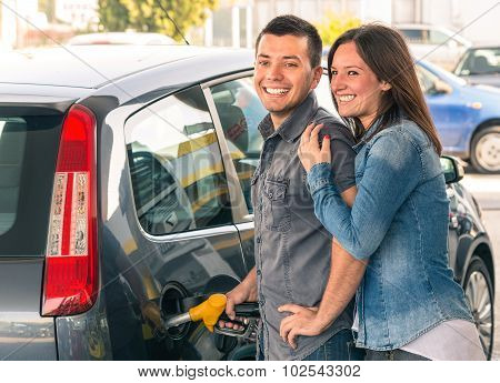 Happy Couple At Fuel Station Pumping Gasoline At Gas Stand. Portrait Of Young Man And Woman