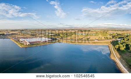 aerial panorama of northern Colorado with a shopping mall, freeway, bike trail and numerous ponds and reservoirs with Front Range of Rocky Mountains ion a horizon
