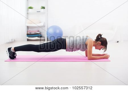 Fit girl in plank position on mat at home the living room exercise for back spine and posture Concep