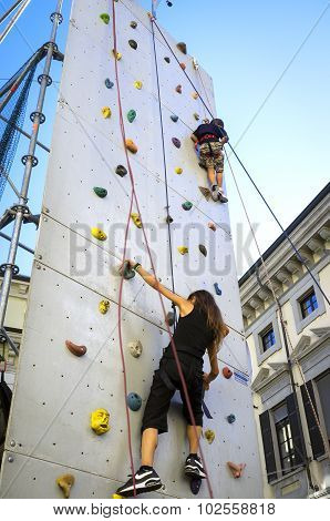 Guys on an artificial climbing wall. Color image