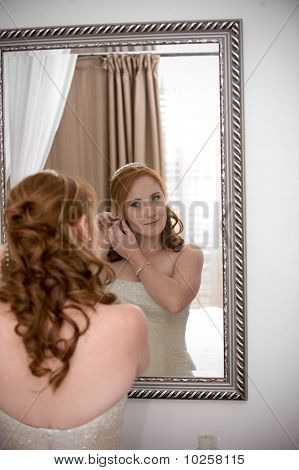 sexy beautiful bride inserting her earrings in whilst smiling